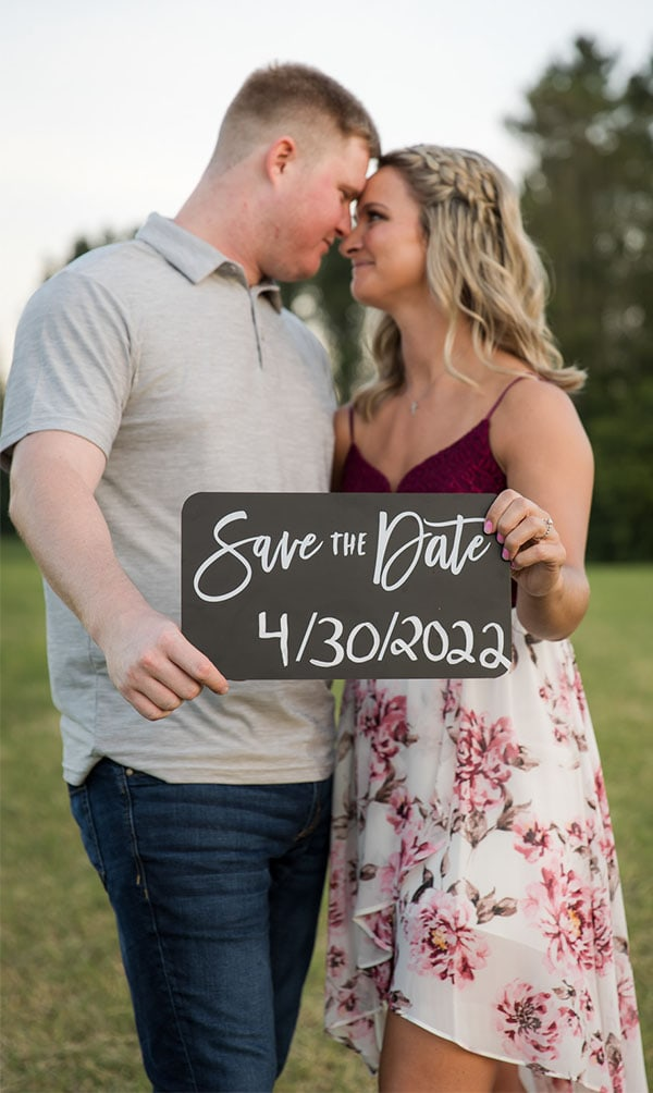 Engaged couple holding a save the date sign